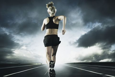 42d83f41c5452 Caucasian woman running on remote road under dramatic sky