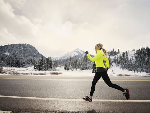 Caucasian woman running on snowy road