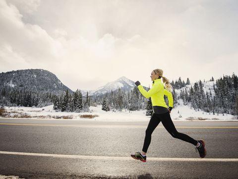 Caucasian woman running on snowy road