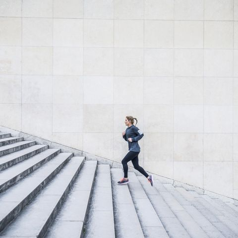 Caucasian woman running up staircase