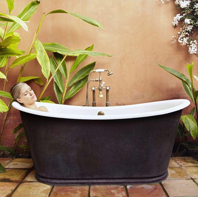 caucasian woman soaking in old fashioned tub