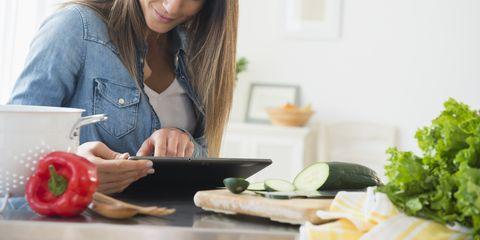 Caucasian woman using digital tablet for recipe