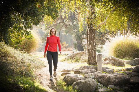 una mujer camina entre árboles y rocas