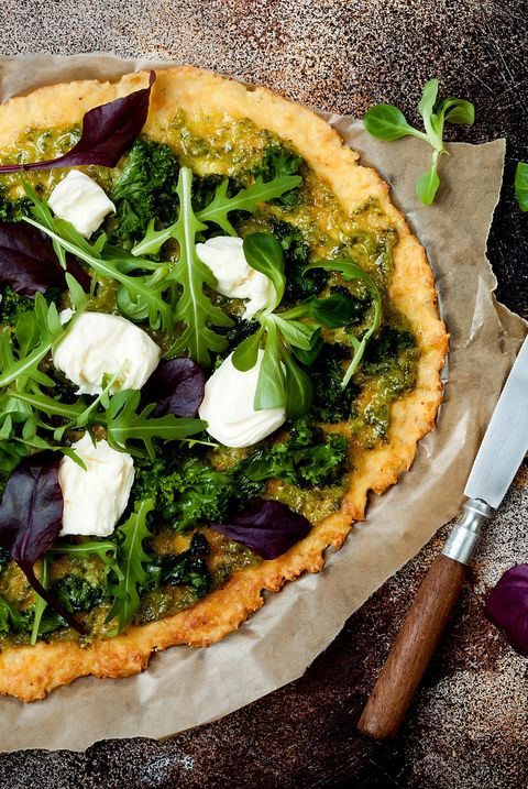 Cauliflower pizza crust with pesto, kale, mozzarella cheese and greens