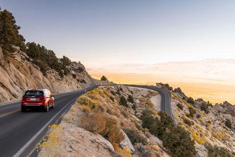 Road, Vehicle, Mountainous landforms, Car, Yellow, Luxury vehicle, Mountain, Sky, Highway, Road trip,