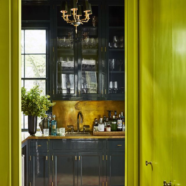 dark glossy cabinets in a bar with brass hardware and countertops and backsplash