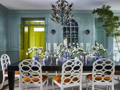 a robins egg blue dining room with a long dining table surrounded by chairs and topped with flowers