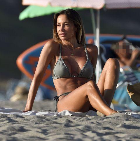 la bailarina, con un bikini en color verde, en una toalla en la arena