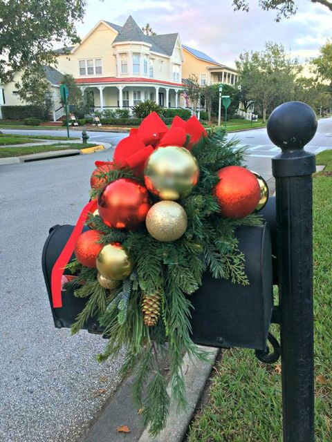 black mailbox and post draped with christmas greenery with gold and red christmas balls, a pine cone and a red velvet bow