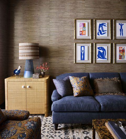 brown dried water hyacinth covered walls, blue sofa, and a grid of colorful artwork by henri matisse behind