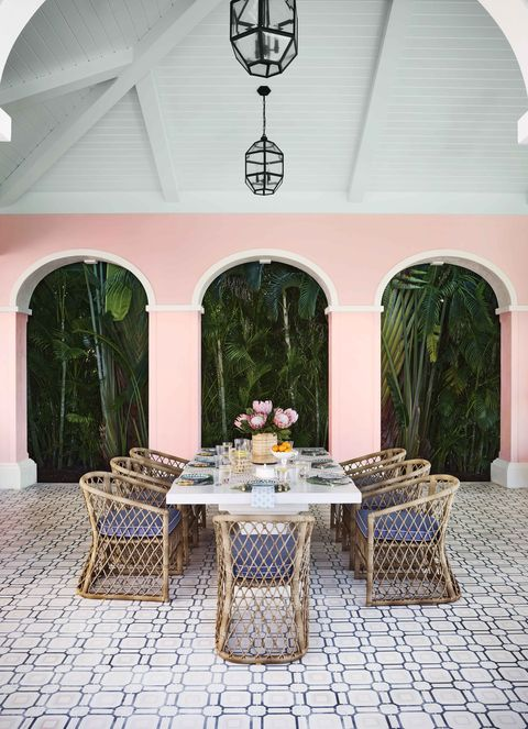 a white table with rattan chairs set for 8 on the terrace in naples, florida