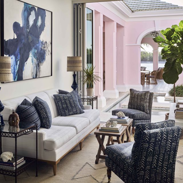 a sofa with two navy bluechairs in a room that opens up to an outdoor terrace