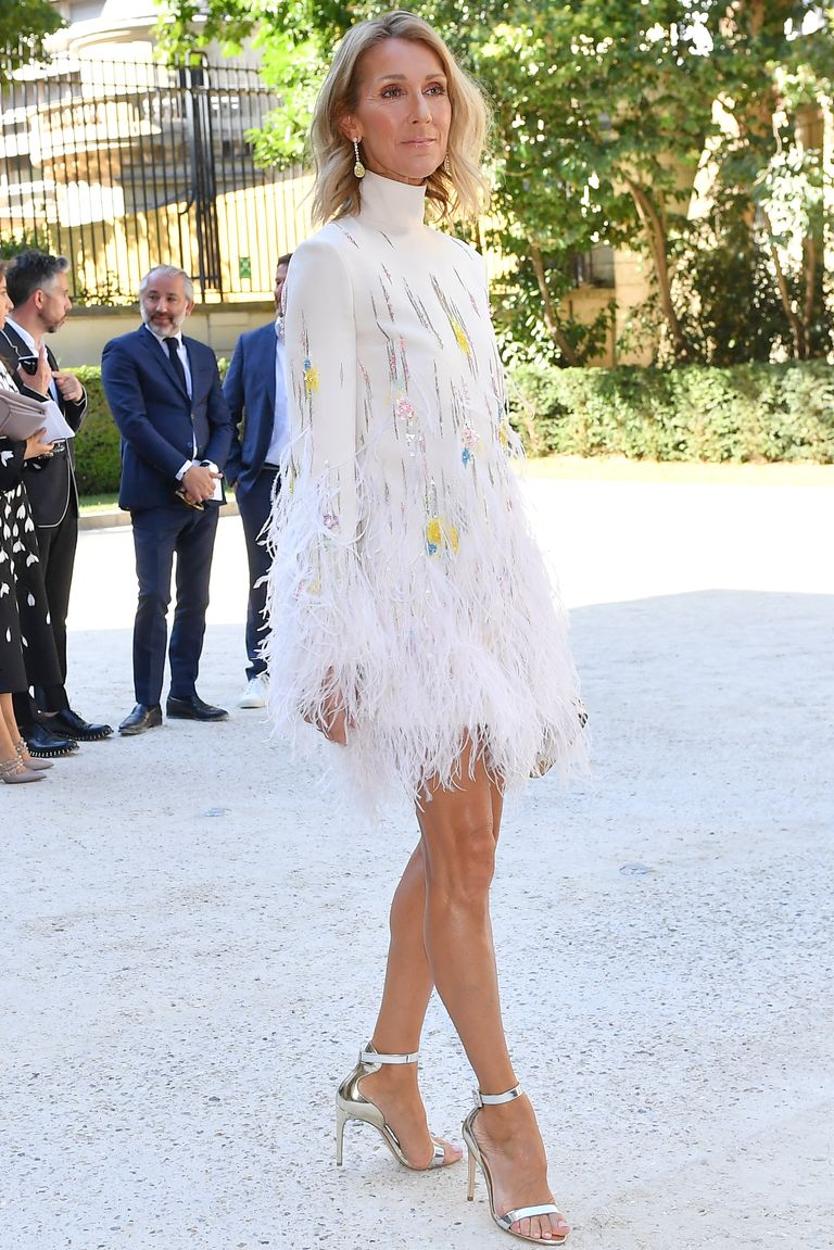 The singer turned heads in a white feathered minidress, silver heels, and yellow drop earrings at the Valentino Haute Couture show during Paris Fashion Week.