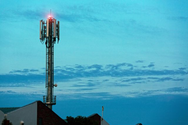 cellphone base station towers over factory roofs against a moody dawn sky