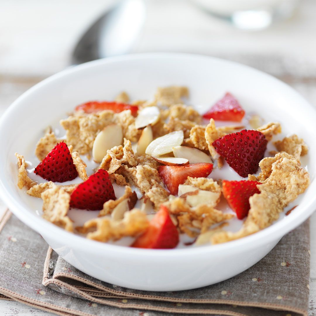 cold cereal with nuts, strawberries, and milk
