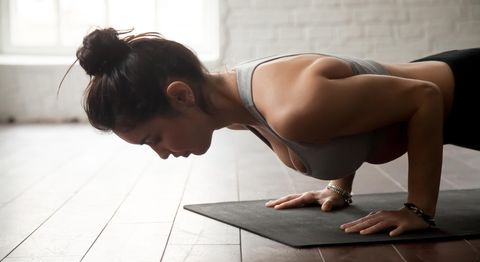 Young attractive woman in chaturanga dandasana pose, loft studio