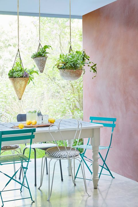patio dining area with pink chalk painted wall and hanging plants