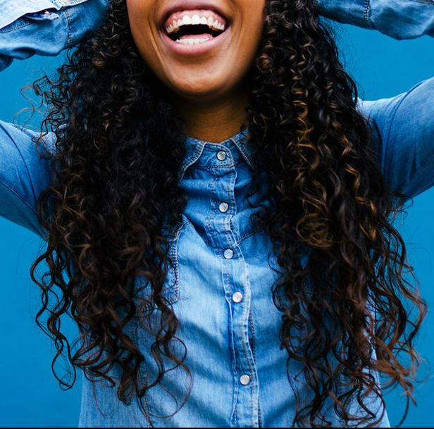 woman with long curly hair in chambray shirt