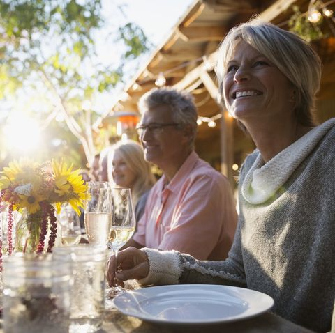 Smiling woman enjoying sunny dinner party