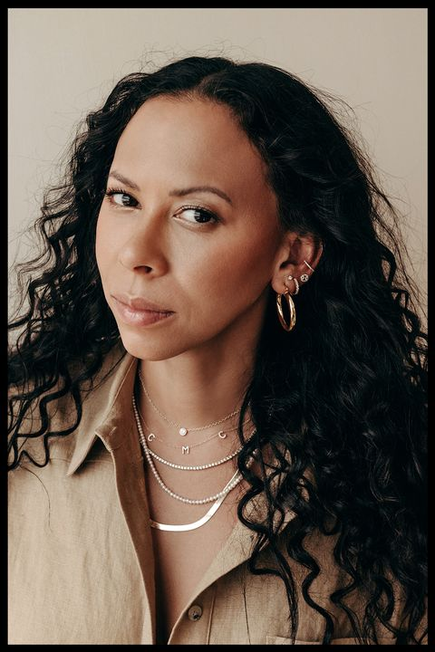 bychari jewelry designer chari cuthbert wearing earrings from her line on a brown background