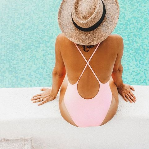 woman in swimsuit and hat by pool