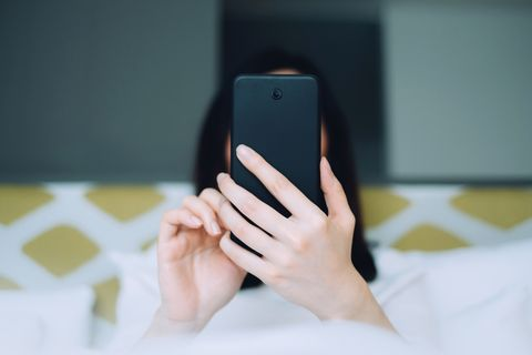 Portrait of woman using mobile phone while lying on bed