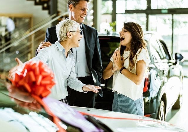 cheerful adult daughter feeling surprised while her parents bought her a car in a showroom