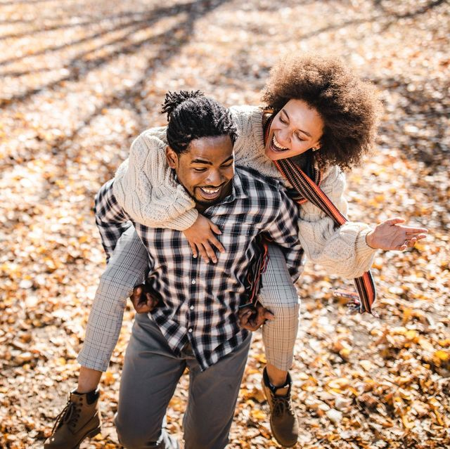 cheerful couple doing a piggyback ride in changing fall leaves