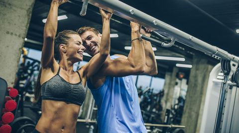 Cheerful athletic couple having fun while exercising in a gym.