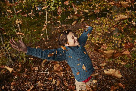 cheerful boy enjoying amidst falling autumn leaves
