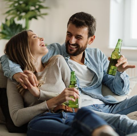 cheerful couple having fun while drinking beer at home