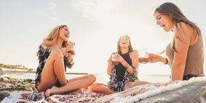 Cheerful Female Friends Having Drink At Beach