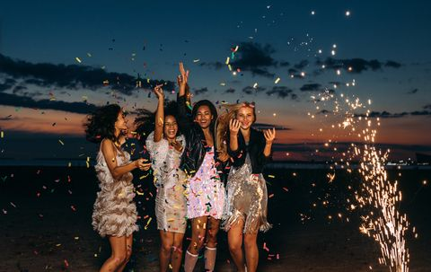 cheerful female friends partying at beach during sunset