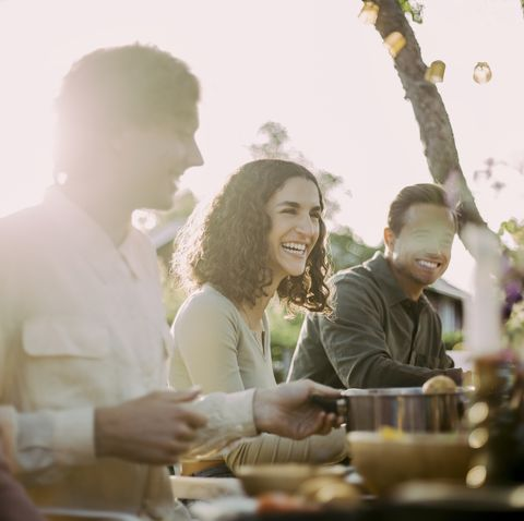 cheerful female with friends sitting in backyard at garden party