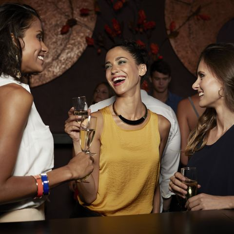 cheerful friends enjoying champagne in nightclub