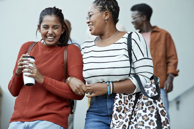 cheerful friends moving down arm in arm at campus