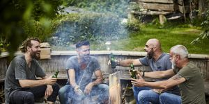 Cheerful friends sitting together at camp fire drinking beer