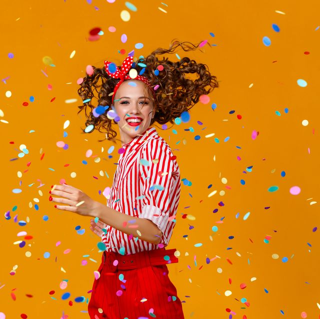 cheerful funny young woman with festive confetti on yellow
