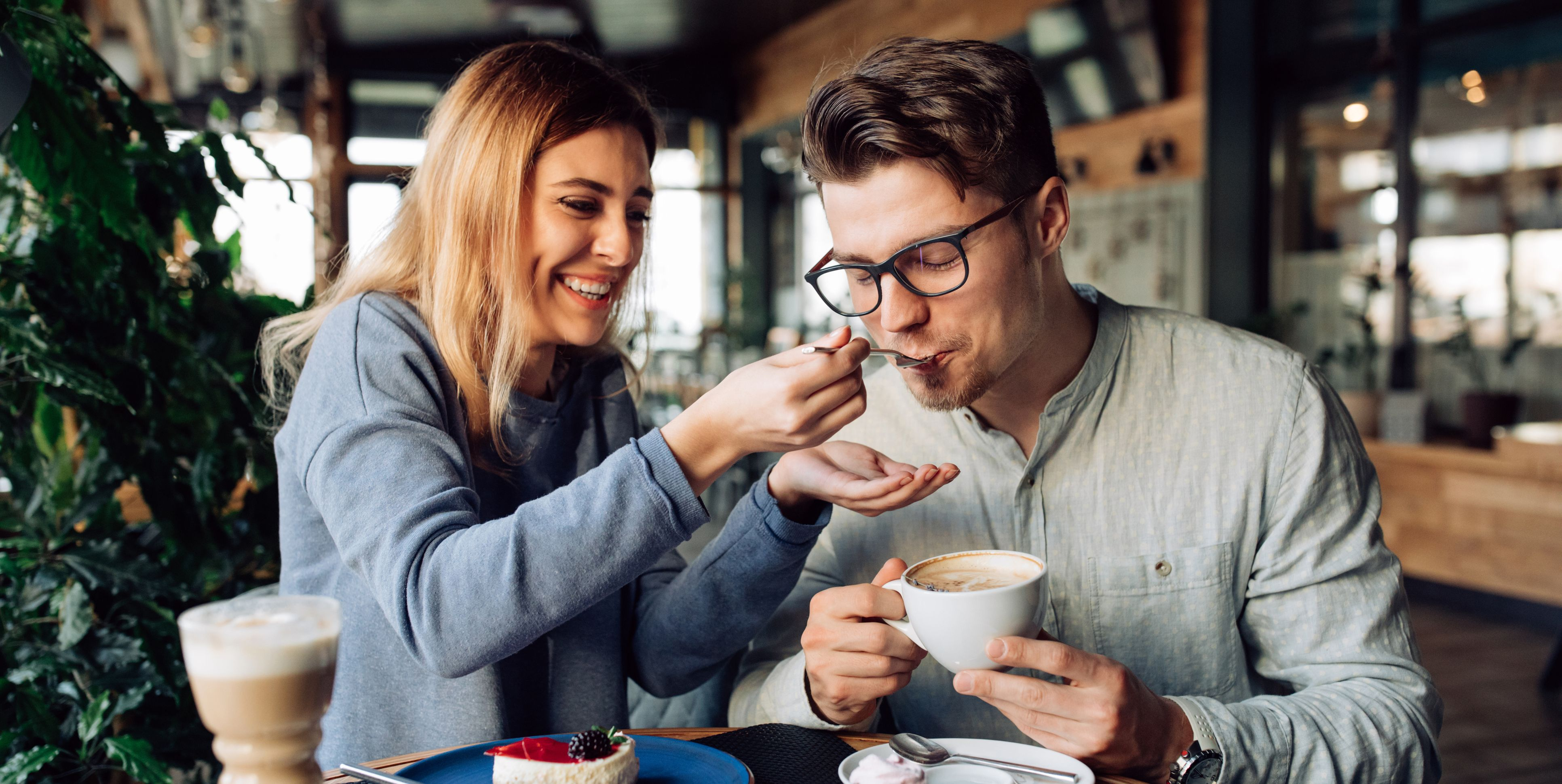Cheerful girl feeding her boyfriend, while resting at cafe