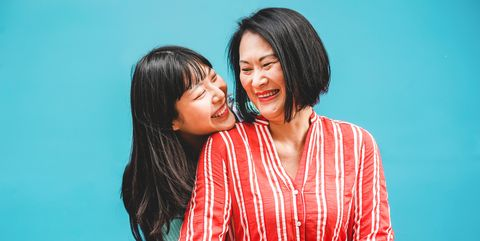 Cheerful Mother And Daughter Against Blue Background