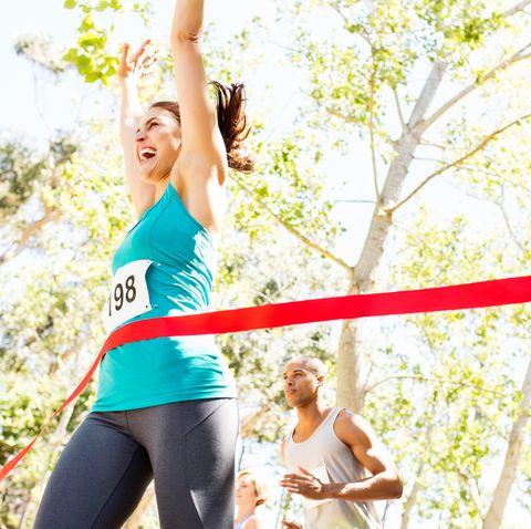 cheerful woman crossing finish line of marathon