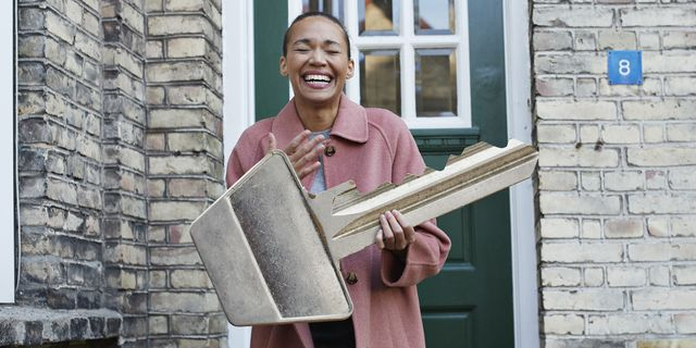 cheerful woman holding large key outside new house
