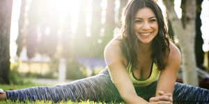 Cheerful woman practicing yoga while exercising in park