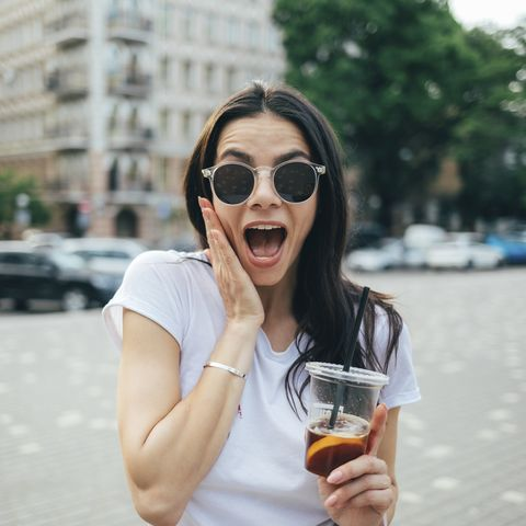 cheerful woman wearing sunglasses with mouth open standing in city