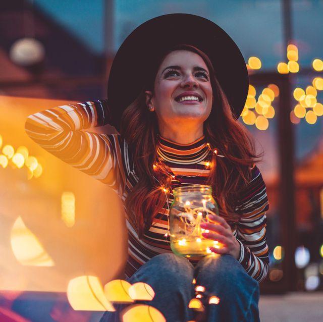 cheerful woman with christmas lights
