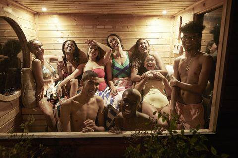 Cheerful young friends enjoying sauna