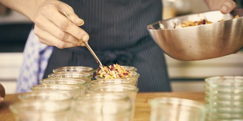 Chef filling plastic containers with portions of food