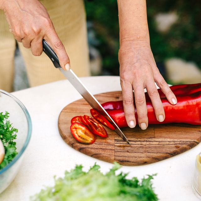 person cutting roasted pepper with chef's knives