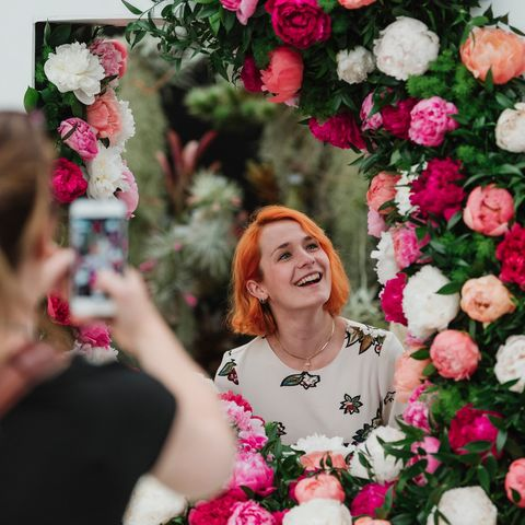 A visitor poses for pictures in the Primrose Hall 'Love Peonies' display in the Great Pavilion at RHS Chelsea Flower Show 2019.