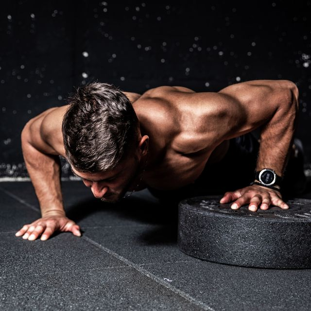 push ups, young strong sweaty focused fit muscular man with big muscles performing push ups with one hand on the barbell weight plate for training hard core workout in the gym
